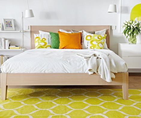 dormitorio con aire minimalísta y retro por los motivos del suelo y cojines